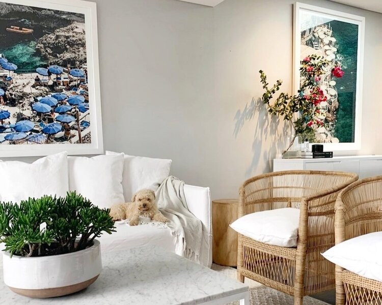 Greta's own lounge room features statement artworks and crisp, white tones throughout.